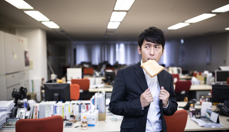 残業中にパンを食べる社員