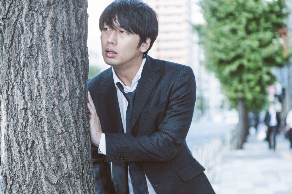 木にもたれかかる男性