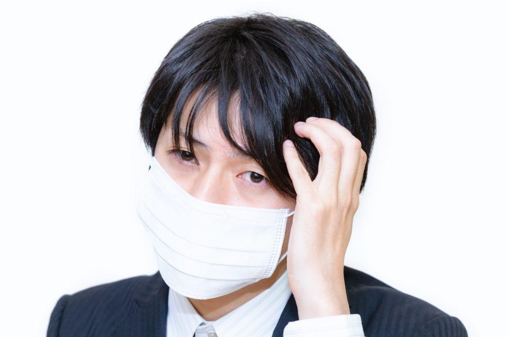 風邪を引いて頭痛の男性